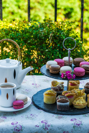 Tea with cakes and macaroons set up in the garden Stock Photo