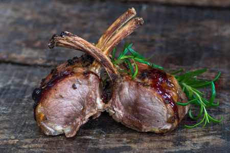 Roasted rack of lamb chops garnished with rosemary on wooden table
