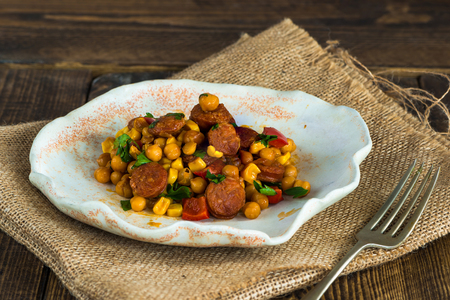 sausage pot: Chorizo and chickpeas braised in cider on wooden table