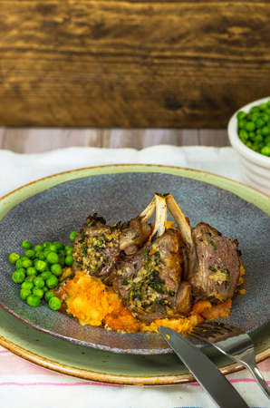 Rosemary lamb chops dinner with carrot and parsnip mash and green peas Stock Photo