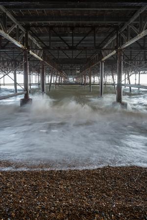 Waves crushing against pillars under the Hastings pier - long exposure