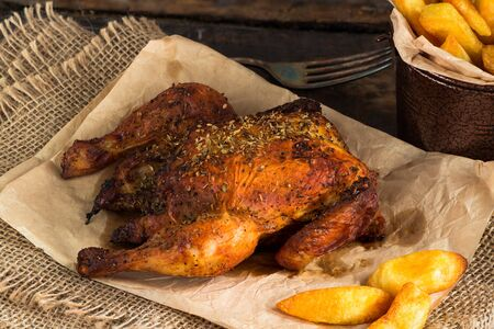 Roasted spatchcock poussin with potato chips on wooden table Фото со стока