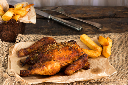 Roasted spatchcock poussin with potato chips on wooden table Imagens - 82016434