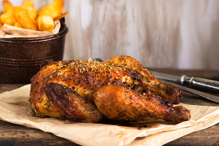 Roasted spatchcock poussin with potato chips on wooden table Stock Photo