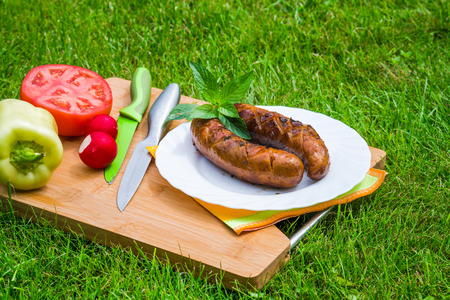 Grilled BBQ sausages on a plate set in the garden Stock Photo