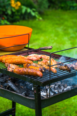 BBQ in the garden - selection of meat on flaming grill - selective focus Stock Photo