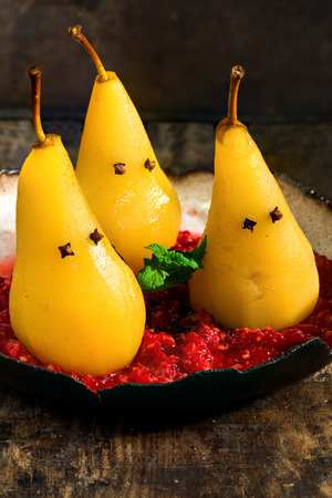 Pears poached in sweet syrup on crushed raspberries, presented as ghosts. Halloween food idea.