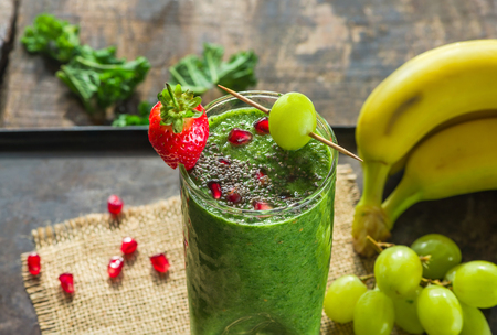 smooth: Healthy green kale and grapes smoothie garnished with chia and pomegranate seeds