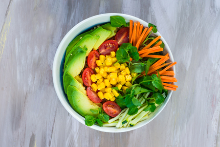 Vegan Buddha bowl with quinoa, avocado, carrots, sweetcorn, tomatoes and courgette - top view Stock Photo