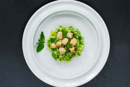 Scallops on minted pea risotto garnished with fresh mint - top view Stock Photo