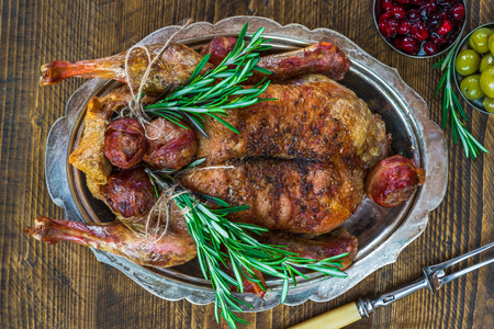 Festive roast duck on wooden table - top view