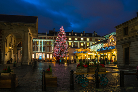 LONDON - NOVEMBER 30, 2017: Big decorated Christmas tree in Londons Covent Garden glowing with festive lights attracts thousands of  Londoners and tourists during the festive season