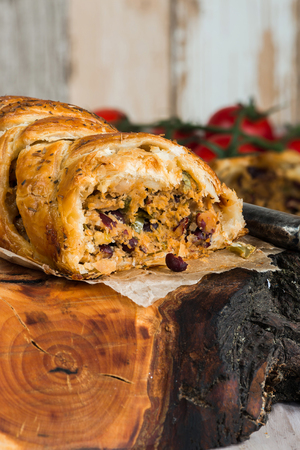 Pork roll - spicy sausage meat with chillies and beans in puff pastry on wooden table