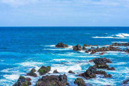 View of sea and waves crashing against stony beach in Puerto de la Cruze, Tenerife, Canary Islands Stock Photo