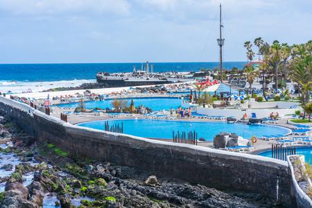 PUERTO DE LA CRUZ, TENERIFE - 19 MARCH 2018: Tourists enjoy sun in public saltwater pools Lago Martianez in Puerto de la Cruz located on the north coast of Tenerife - the largest of Spain's Canary Islands.