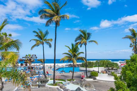 PUERTO DE LA CRUZ, TENERIFE - 19 MARCH 2018: Tourists enjoy sun in public saltwater pools Lago Martianez in Puerto de la Cruz in Tenerife - the largest of Spain's Canary Islands.