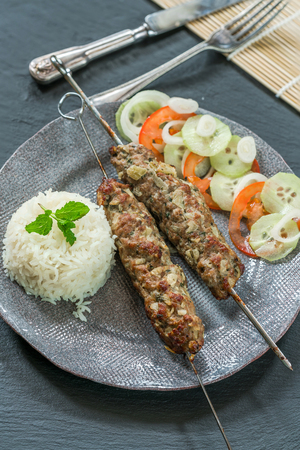 Minted lamb kebabs on skewers with rice and cucumber and tomato salad - high angle view
