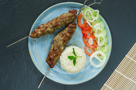 Minted lamb kebabs on skewers with rice and cucumber and tomato salad - top view Stock Photo