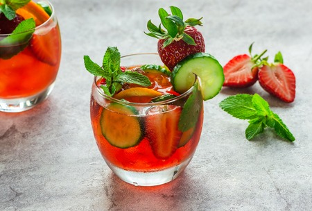 Traditional Pimms cocktail with lemonade, strawberries, cucumber, orange and mint