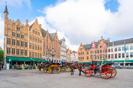 BRUGES, BELGIUM - APRIL 23, 2018: The Markt of Bruges in the heart of the city is a popular tourist spot. Historical buildings around the square include 12th-century belfry and the Provincial Court Editorial