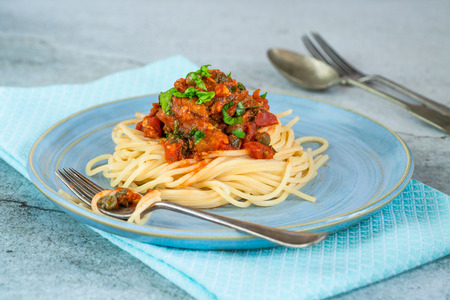 Spaghetti with sardines in tomato sauce garnished with fresh parsley Archivio Fotografico