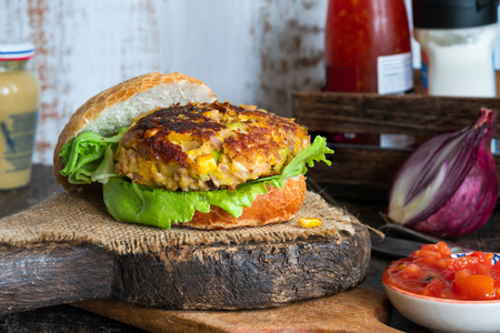 Tuna and sweetcorn burger with tomato salsa in a bun Imagens