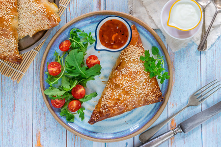 Giant chicken samosas with mango chutney and fresh salad, sprinkled with sesame seeds - top view