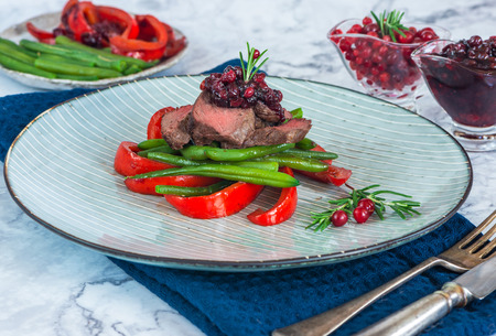 Sliced venison steak with lingonberry sauce, roast red peppers and green beans Stock Photo