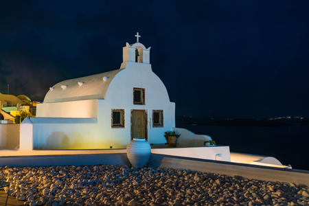 Santorini landscape with night view of whitewashed Greek orthodox church in Oia, Greece