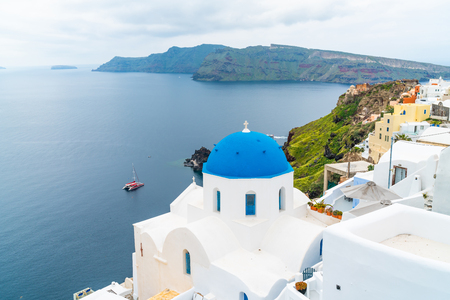 Traditional whitewashed church with blue dome in Oia with view of caldera and Aegean Sea. Santorini, Greece