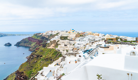 View of Oia, a coastal town on Greek island Santorini. The town has whitewashed houses carved into the rugged clifftops, and overlooks a vast caldera filled with water. 免版税图像