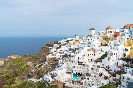 View of Oia, a coastal town on Greek island Santorini. The town has whitewashed houses carved into the rugged clifftops, and overlooks a vast caldera filled with water. Фото со стока