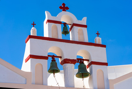 Whitewashed Bell Tower against blue sky in Oia, Santorini, Greece
