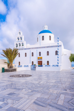 Beautiful white Church of Panagia with blue dome in the main square of Oia, Santorini, Greece