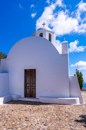 Traditional whitewashed Greek church on the hill near Oia agaimst blue sky, Santorini, Greece Фото со стока