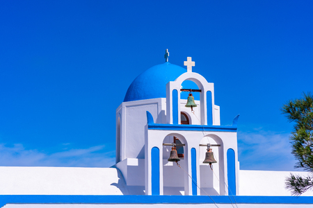 Blaue Kuppel und Glockenturm einer weiß getünchten griechischen Kirche auf dem Hügel in der Nähe von Oia, Santorini, Griechenland