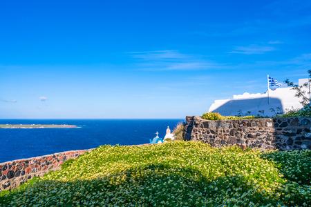 Santorini landscape with wild flowers and Aegean Sea in Oia, Greece
