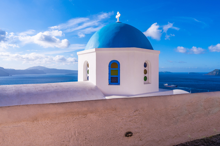 Blue dome of a traditional whitewashed church in Oia against blue sky with  view of caldera and Aegean Sea, Santorini, Greece Фото со стока