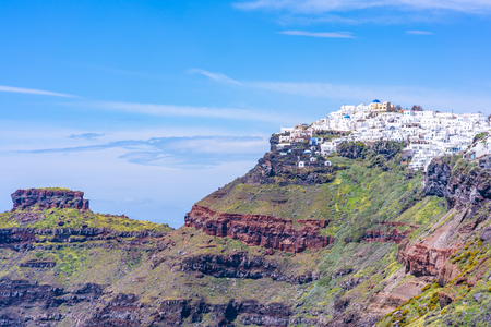 Santorini landscape - distant view of Fira perched on rugged cliff, Greece