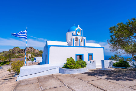 Traditional whitewashed Greek church with blue dome on the hill near Oia, Santorini, Greece