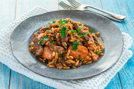 Giouvetsi - traditional Greek baked dish with beef and orzo pasta in tomato sauce.