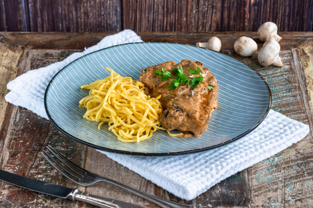 Pork chops in creamy cajun sauce with button mushrooms and egg noodles garnished with parsley.