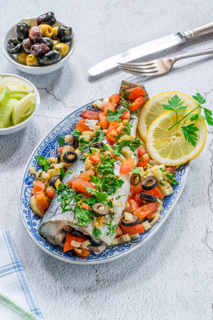 Mediterranean sea bass stuffed with tomatoes, lemons, fennel and olives - high angle view. Greek cuisine. Stok Fotoğraf - 123088441