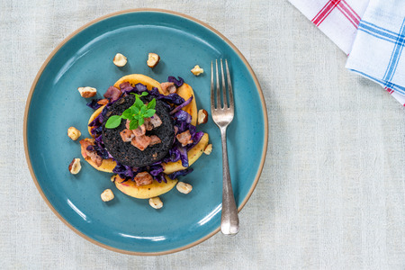 Warm salad of red cabbage, black pudding and apple with crispy bacon and crushed hazelnuts - overhead view Stockfoto