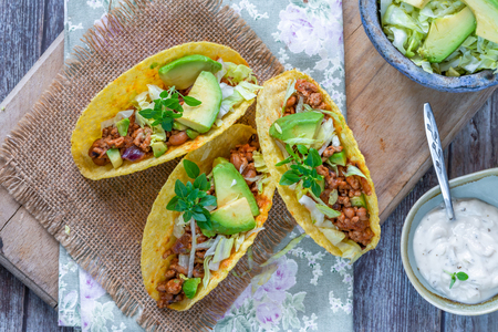 Smoky Mexican pork and bean tacos with lettuce and avocado salad