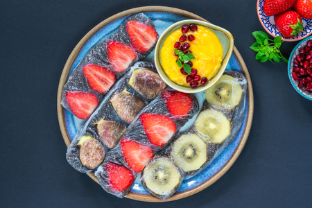 Chia seeds and fruit rice paper rolls with mango dipping sauce - top view
