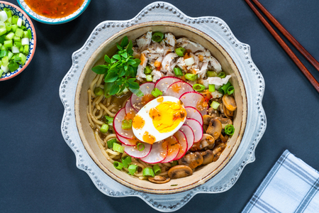 Ramen noodles with chicken, egg, mushrooms and radish sprinkeld with chili sauce and sesame seeds - top view Reklamní fotografie