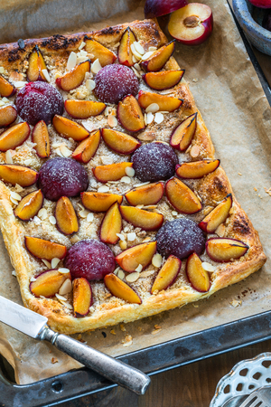 Plum and almond pastry dusted with icing sugar - high angle view Reklamní fotografie