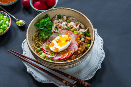 Ramen noodles with chicken, egg, mushrooms and radish sprinkeld with chili sauce and sesame seeds - high angle view