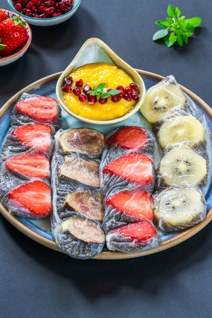 Chia seeds and fruit rice paper rolls with mango dipping sauce